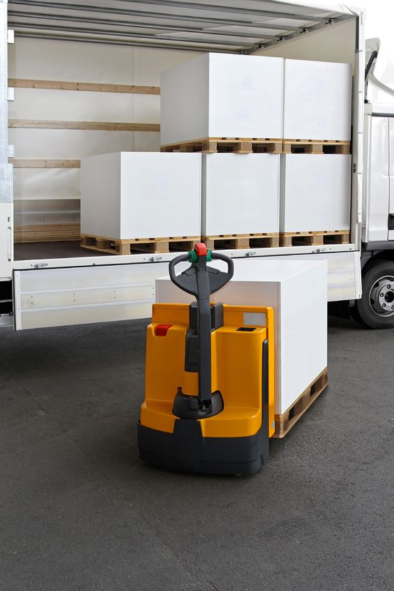 forklift truck loading pallets of paper in truck